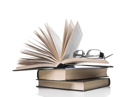 pile of books with one book open and eyeglasses  on white background