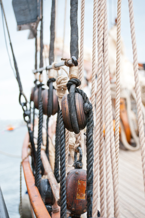brigg: Marine ropes and tackles on the tall ship. Old wooden block with rope on the sail.