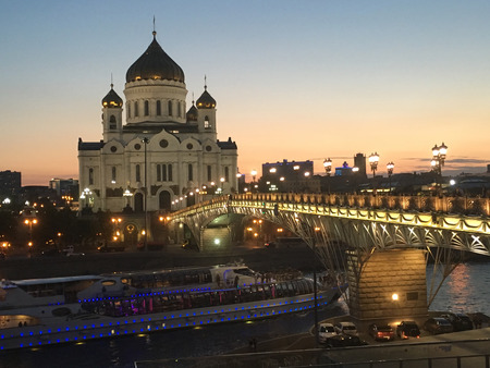 tallest bridge: Moscow, Russia- June 20, 2016: Majestic orthodox Cathedral of Christ Saviour illuminated at dusk on bank of Moscow river and cruise boat. It is tallest Orthodox church in world Editorial