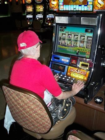 tragamonedas: HENDERSON, NEVADA  EE.UU. - 3 de abril: An mujer de imagen El jugar del las máquinas de ranura at Green Valley Ranch Casino el 3 de abril de 2008.