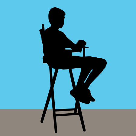 directors: a young male sitting in a directors chair.