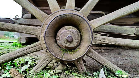 old wood farm wagon: An image of an old broken wagon wheel.