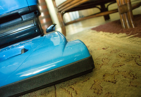 An image of a upright vacuum cleaner on an oriental rug. Foto de archivo