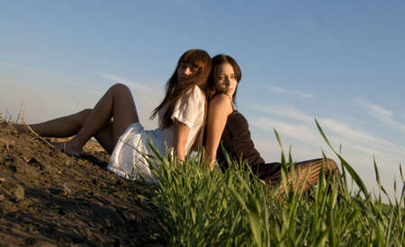 sitting area: Two beautiful girls on the green grass