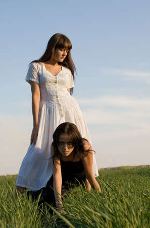 Two beautiful girls on the green grass, one is over the other photo