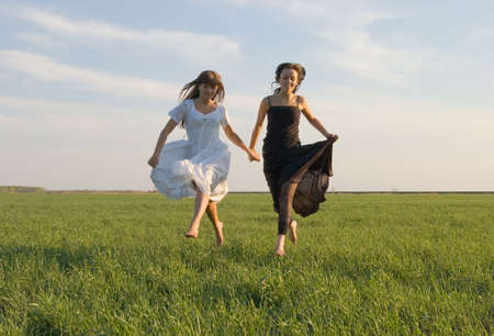 Two beautiful girls running on the green field