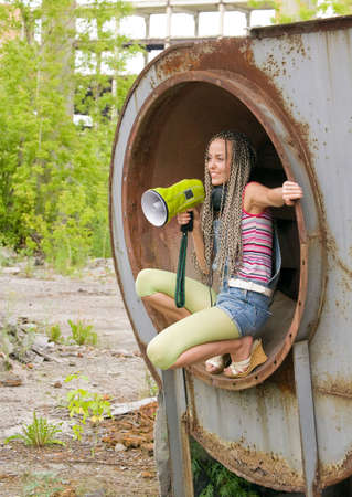 Beauty girl sit in the ring and singing to megaphone photo