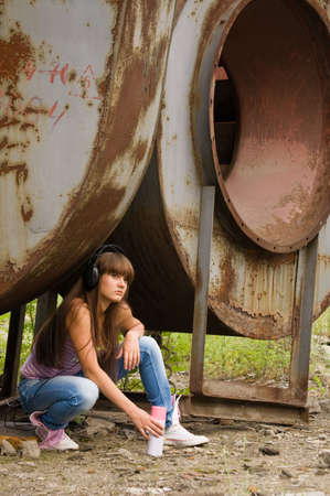 beauty girl with ballon paint sit in headphones near constructions Stock Photo