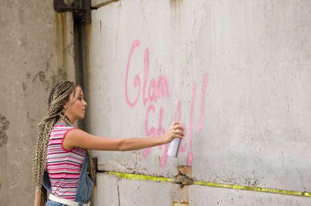 delincuencia: chica en la pintura gris y sucio muro Foto de archivo