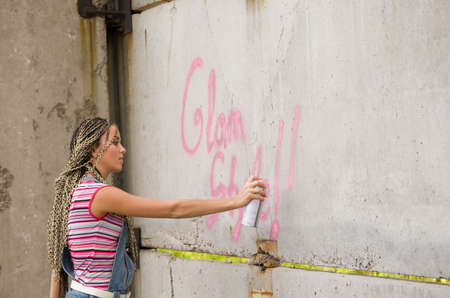 girl painting on the gray and dirty wall Stock Photo