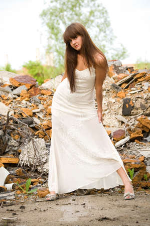 fashionable girl in white dress on the dirty industrial place photo