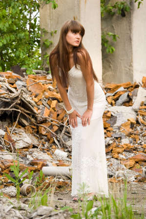 trash the dress: fashionable girl in white dress on the dirty industrial place
