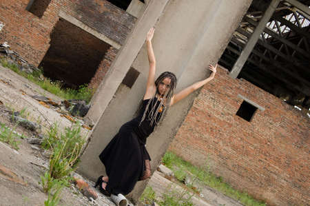 fashionable girl in black dress alongside of column on the dirty industrial place Stock Photo - 3898724