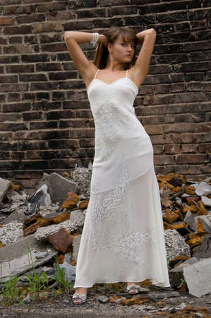 trash the dress: fashionable girl in white dress on the dirty industrial place and brick background Stock Photo