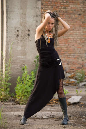 trash the dress: fashionable girl in black dress on the dirty industrial place and brick background