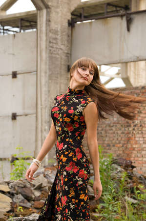 trash the dress: fashionable girl in dress with flowers on the dirty industrial place and wall background Stock Photo