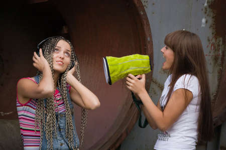 girl singing in megaphone for another girl who listing music in headphones photo
