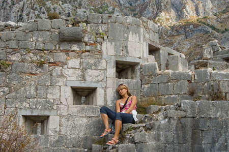 stockade: beauty girl on stair beside fortress in the Montenegro Stock Photo
