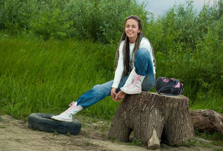 smiling girl sitting on a stump on dirty beach background photo