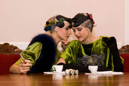 two beauty talking girls sit sitting at the wood table Stock Photo