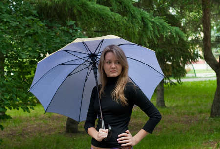 beauty girl stay with umbrella in the park on trees background Stock Photo - 5241327