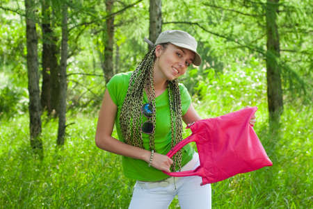 beauty girl in the cap with pink bag on the forest background photo