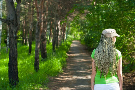 Braided girl walk on footpath in the park with forest Stock Photo - 5481288