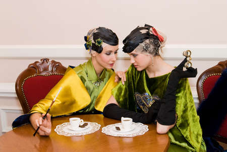 two beauty talking girls sitting at the wood table
