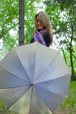 beauty girl with umbrella and violet scarf in the park on trees background Stock Photo - 5512328