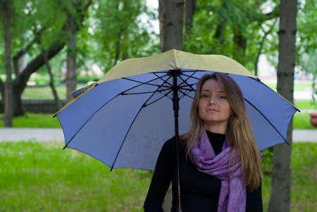 beauty girl with umbrella and violet scarf in the park on trees background Stock Photo - 5512331