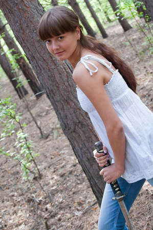 beauty girl in white dress with sword on the trees background Stock Photo - 5557874