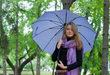 beauty girl with umbrella and violet scarf in the park on trees background Stock Photo - 5557878