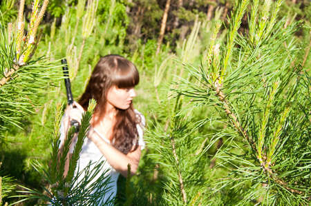 beauty girl in white dress with gun on nature background photo