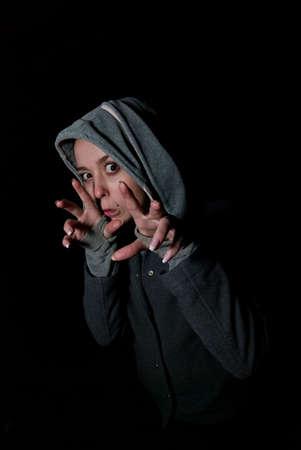 horrify: girl in grey hood horrify on black background