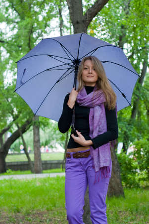 beauty girl with umbrella and violet scarf in the park on trees background Stock Photo - 5580638