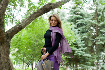 beauty girl with umbrella and violet scarf in the park on trees background Stock Photo - 5594803