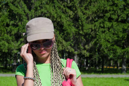 beauty girl in baseball cap looking over sunglasses on the forest background Stock Photo - 5594801