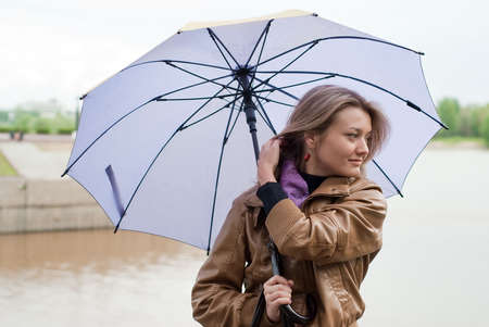 beauty girl in brown jacket and  with violet umbrella on the river background photo