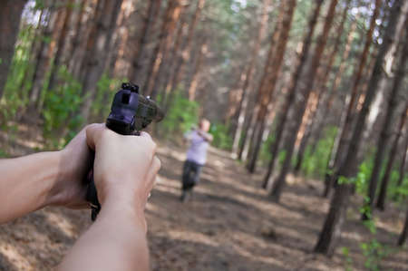 turn about: man in conifer  forest attack killer with gun Stock Photo