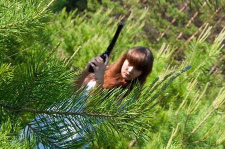 beauty girl in white dress with gun on nature background Stock Photo - 5630283