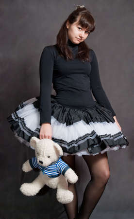 playthings: beauty ballerina with bear in striped shirt on grey background Stock Photo
