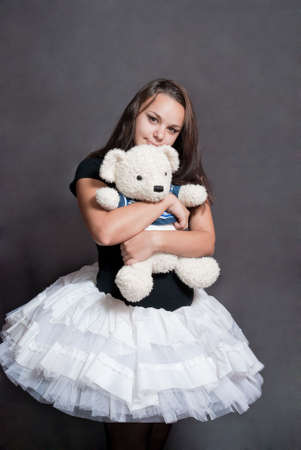 beauty ballerina with bear in shirt on grey background photo