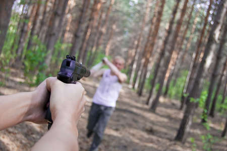 assail: man in conifer  forest attack killer with gun Stock Photo