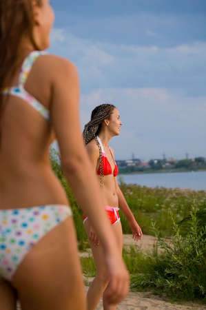 two beauty girls in swimsuit on the nature background photo