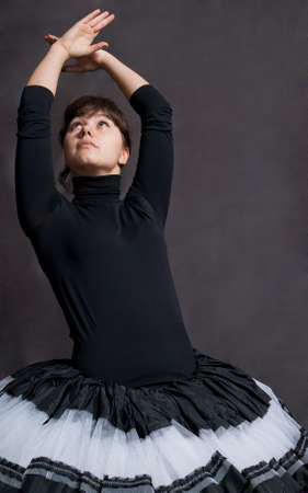 beauty cheerful ballerina in black and white tutu on grey background photo