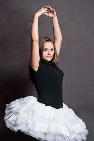 beauty cheerful ballerina in white tutu on grey background photo