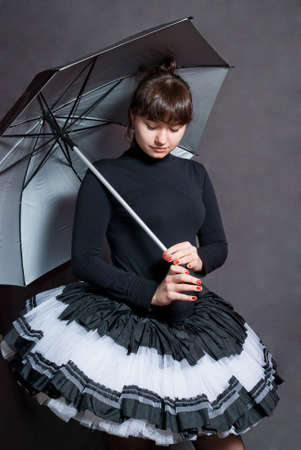 beauty ballerina with silver umbrella on grey background photo