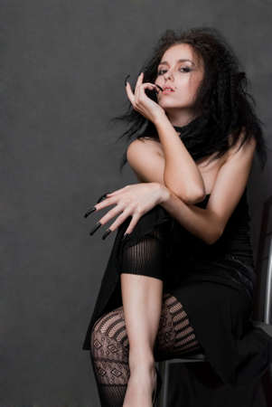 beauty young witch with black nails siting on gray background photo