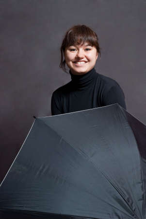 beauty and happy girl with umbrella on gray background photo