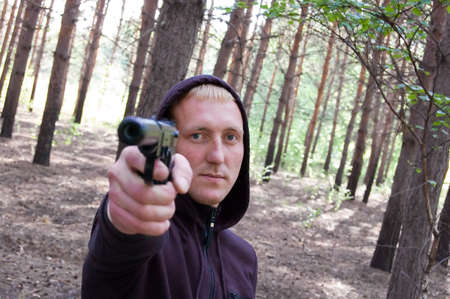 man with blond hair hold at gunpoint on the forest background Stock Photo - 5912662